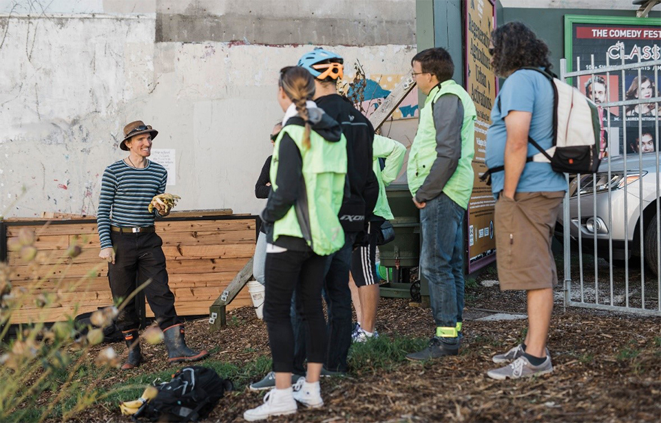 Gardener Levi describes the composting process to bikers at the Organic Market Garden. Photo: Claire Mossong